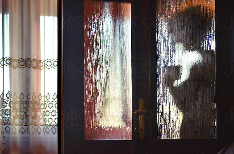 Silhouette of a girl trough glass door,bringing cup of coffee by Marija Anicic for Stocksy United