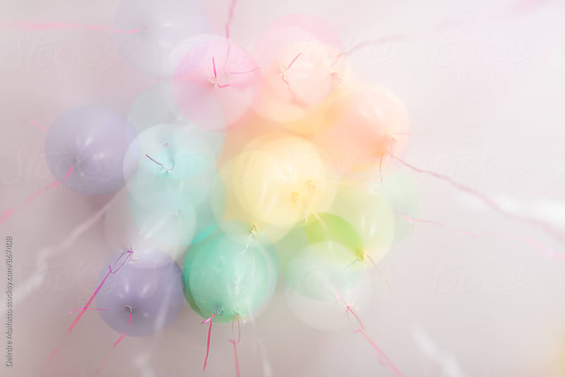 multiple exposure of pastel balloons against a white ceiling by Deirdre Malfatto for Stocksy United
