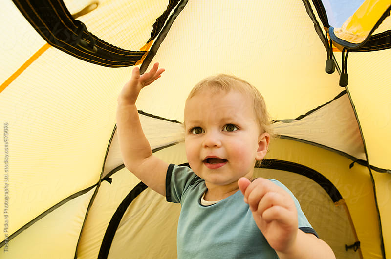 Girl toddler playing inside a tent while on a camping trip, New Zealand. by Thomas Pickard Photography Ltd. for Stocksy United