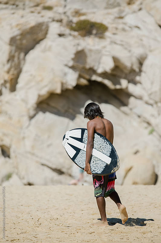 A young surfer walking on a beach holding a board looking down by Ania Boniecka for Stocksy United