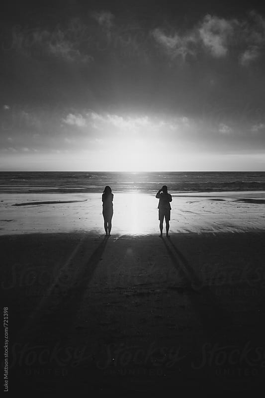 A Woman And Man Stand On The Shore Watching The Sun Set Over The Pacific Ocean by Luke Mattson for Stocksy United