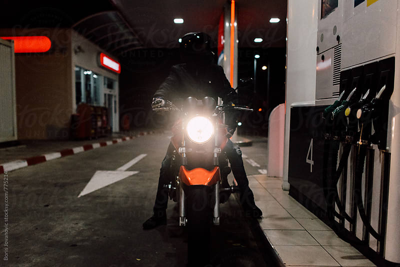 Biker waiting at gas station by Boris Jovanovic for Stocksy United