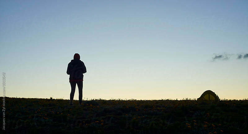 Silhouetted hiker walking back to her tent at dusk. by Jacques van Zyl for Stocksy United
