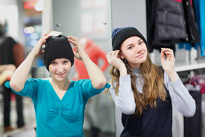 Young women shopping for clothes by Ilya for Stocksy United
