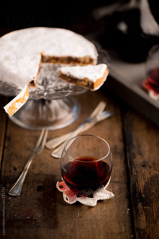 a glass of marsala wine served with a slice of Panforte by Laura Adani for Stocksy United