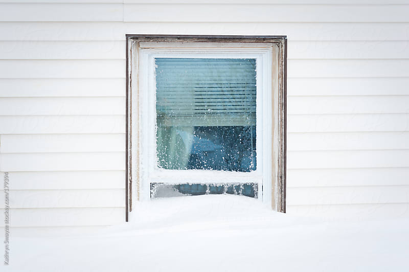 A window is partially hidden from view after a heavy snow fall by Kathryn Swayze for Stocksy United