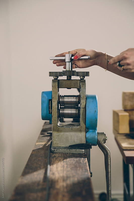 Closeup of a woman's hand handling a metal press by Lior + Lone for Stocksy United