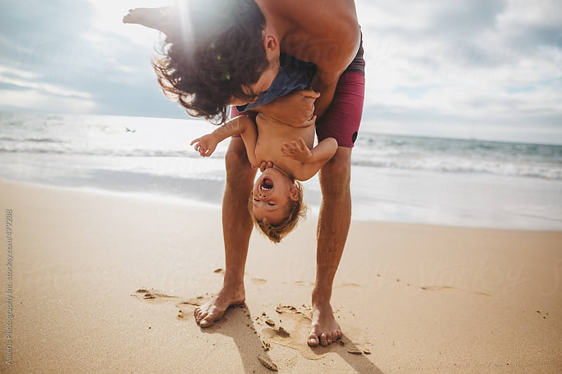 Young dad having fun - tickling - with toddler son on tropical beach by Rob and Julia Campbell for Stocksy United