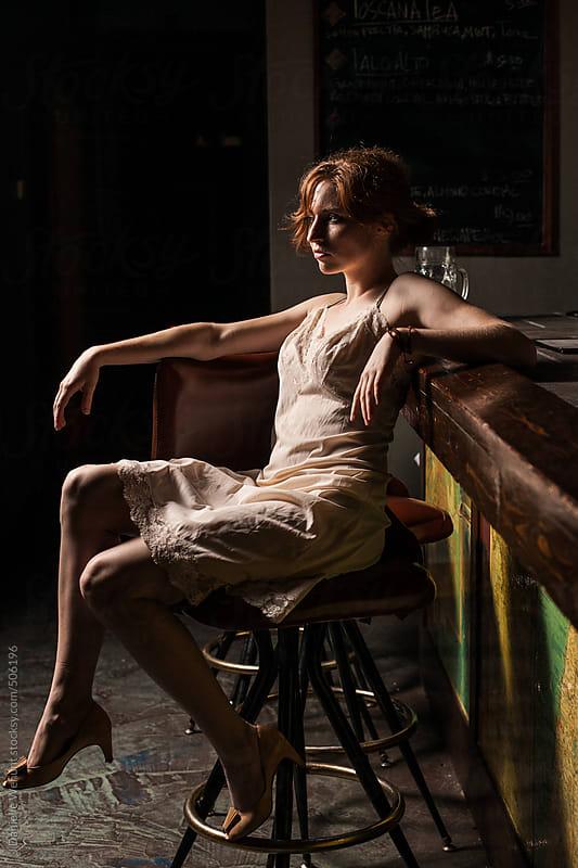 Red headed caucasian woman in lingerie sitting on dimly lit barstool by J Danielle Wehunt for Stocksy United