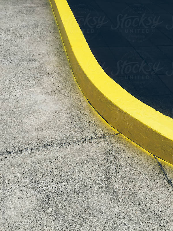 Painted yellow curb and urban sidewalk by Paul Edmondson for Stocksy United