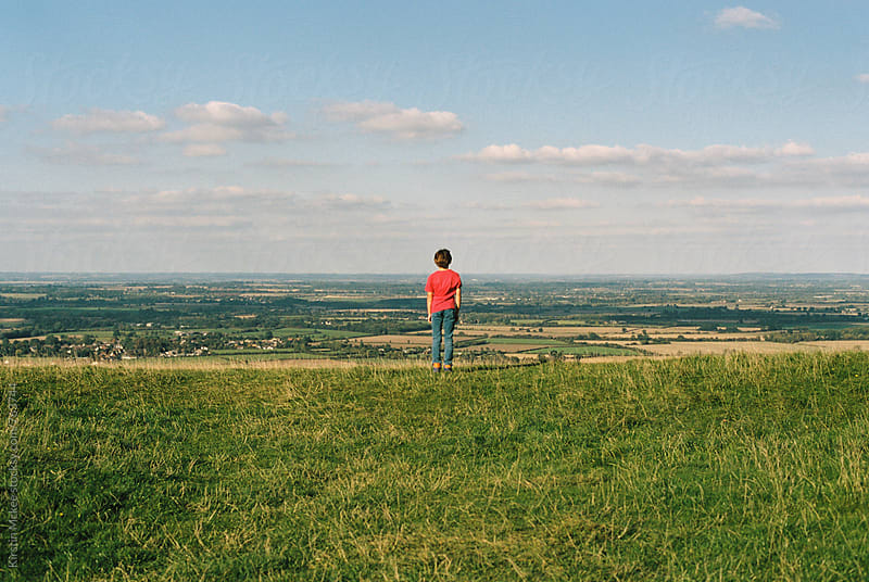 Boy standing on hill and enjoying view across Oxfordshire by Kirstin Mckee for Stocksy United
