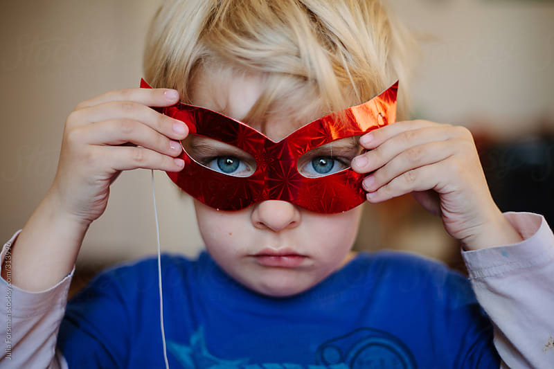 Boy with blue eyes looks through red paper mask. by Julia Forsman for Stocksy United