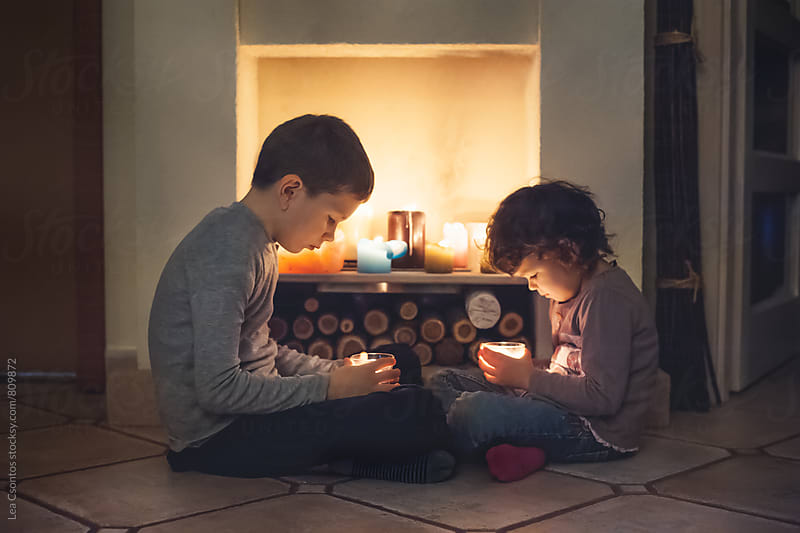 Siblings sitting in front of a fireplace holding candles in their hands and watching the flame by Lea Csontos for Stocksy United