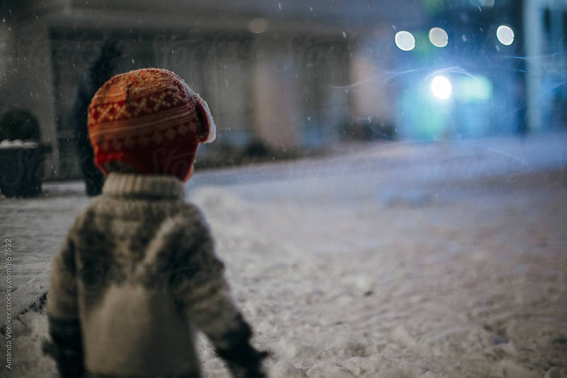 Back View of a Toddler Boy Standing in a Snowstorm  by Amanda Voelker for Stocksy United