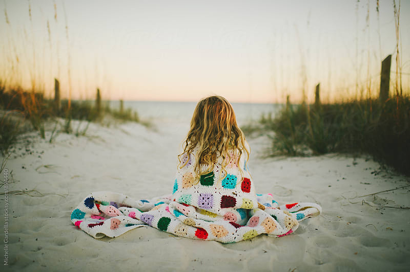Girl on beach with blanket by Michelle Gardella for Stocksy United