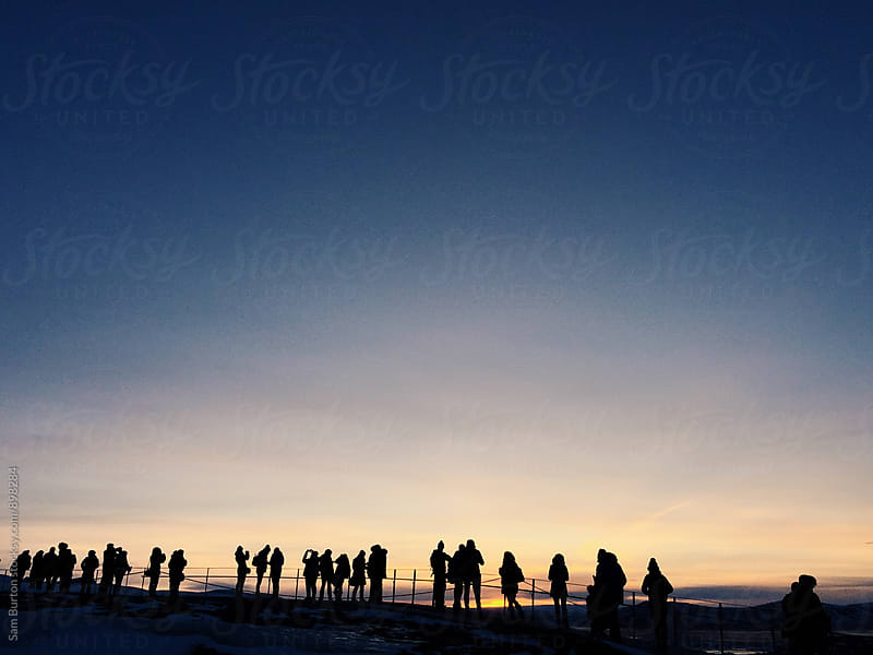 People gather to watch the sunrise by Sam Burton for Stocksy United