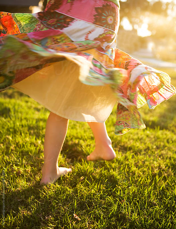 Lower Half Of Girl Twirling Colorful Skirt On Grass by Dina Giangregorio for Stocksy United