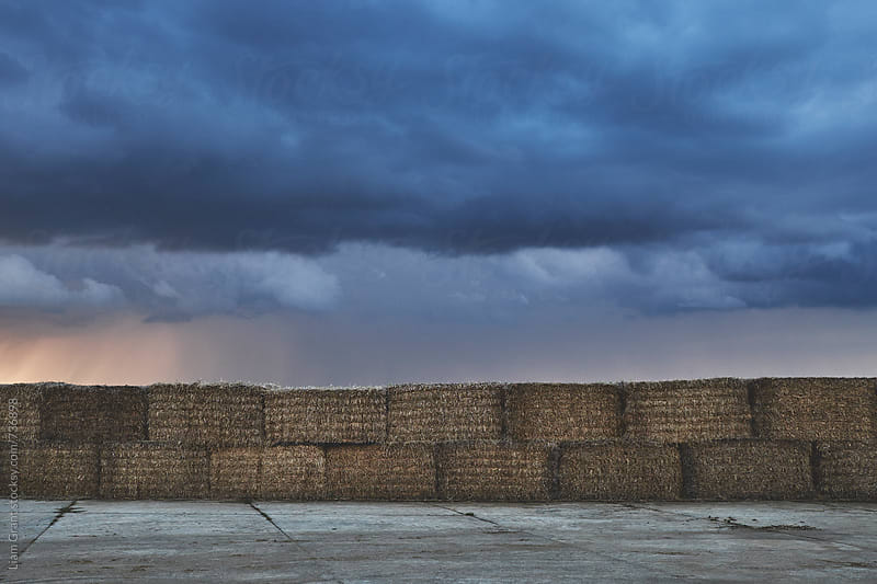 Straw bales stacked below a dark stormy sky at sunset. Norfolk, UK. by Liam Grant for Stocksy United