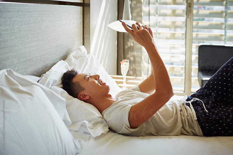 Happy Man Using Mobile Phone In Bed by ALTO IMAGES for Stocksy United