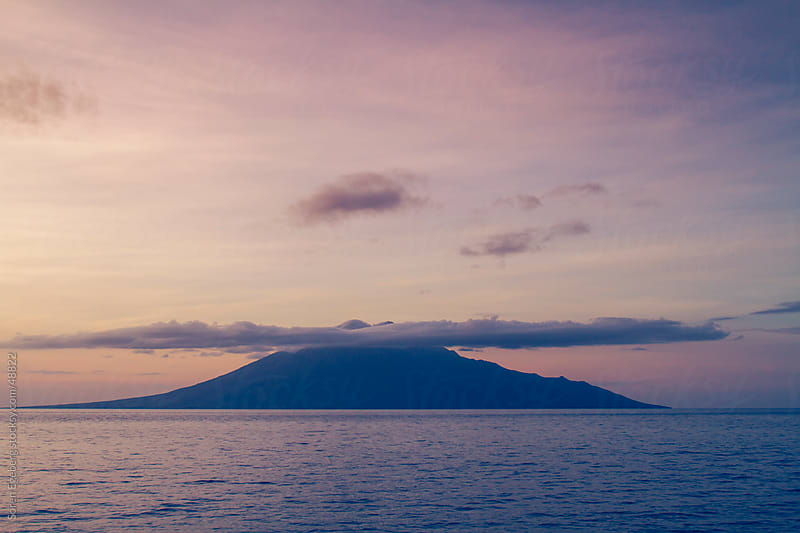 Volcanic island with clouds in the ocean of Indonesia by Søren Egeberg Photography for Stocksy United
