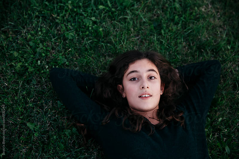 Preteenager girl lying on the grass and looking at camera by Beatrix Boros for Stocksy United