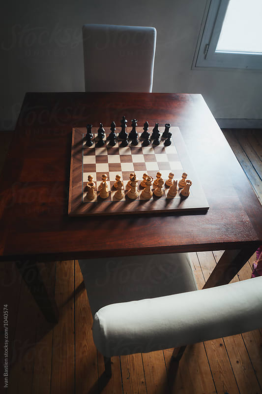 Chess game on a table with two chairs ready to play by Ivan Bastien for Stocksy United