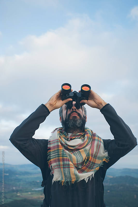Man with binoculars by CACTUS Blai Baules for Stocksy United