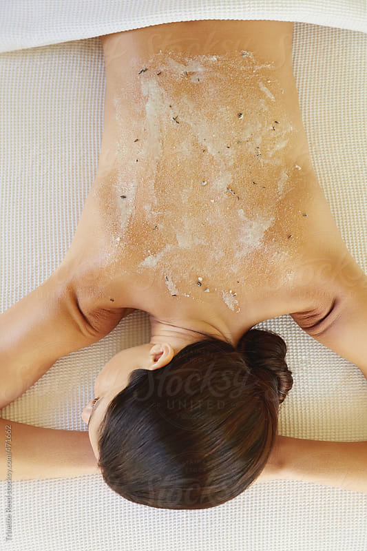 Woman receiving exfoliation salt scrub treatment at luxury spa by Trinette Reed for Stocksy United