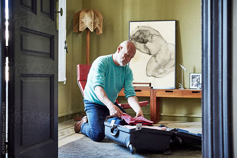 Senior Man Packing Suitcase At Home by ALTO IMAGES for Stocksy United