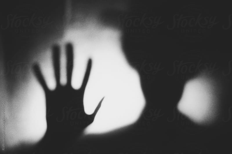Abstract portrait of man's shadow with hand raised, blurred focus by Paul Edmondson for Stocksy United