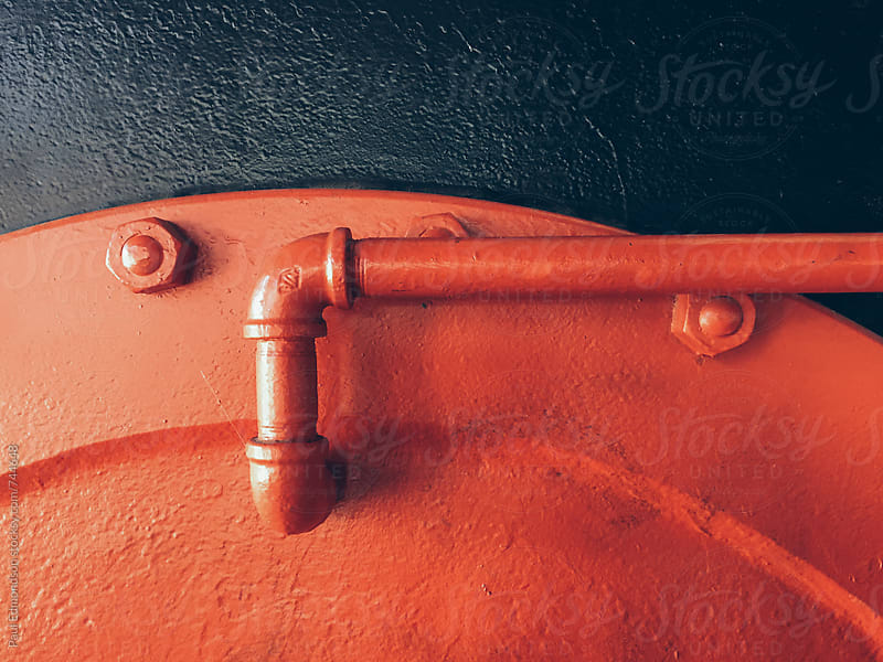 Painted red metal piping and industrial machinery, close up by Paul Edmondson for Stocksy United