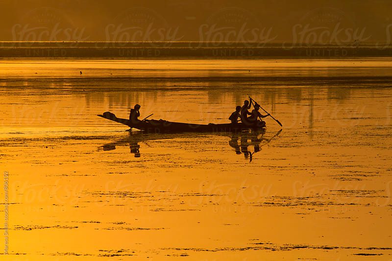 A golden sunset over Dal Lake and silhouetted men paddling their boat by Maresa Smith for Stocksy United