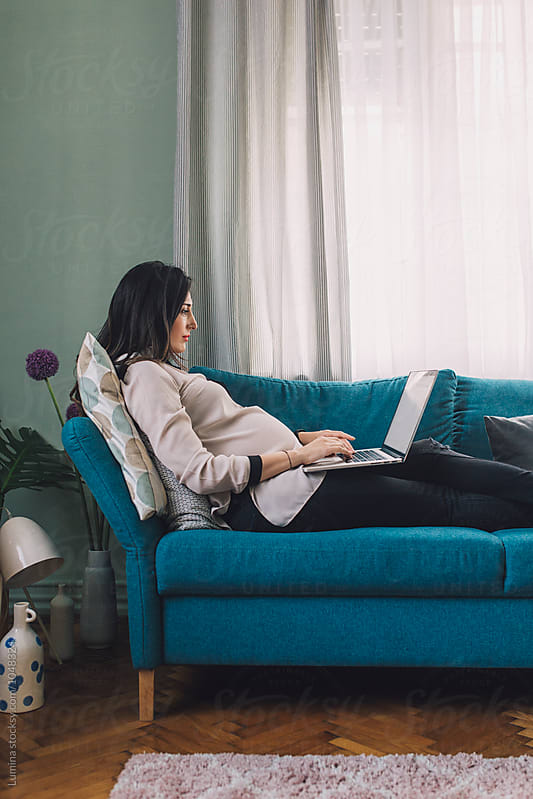 Pregnant Woman Working on a Couch by Lumina for Stocksy United