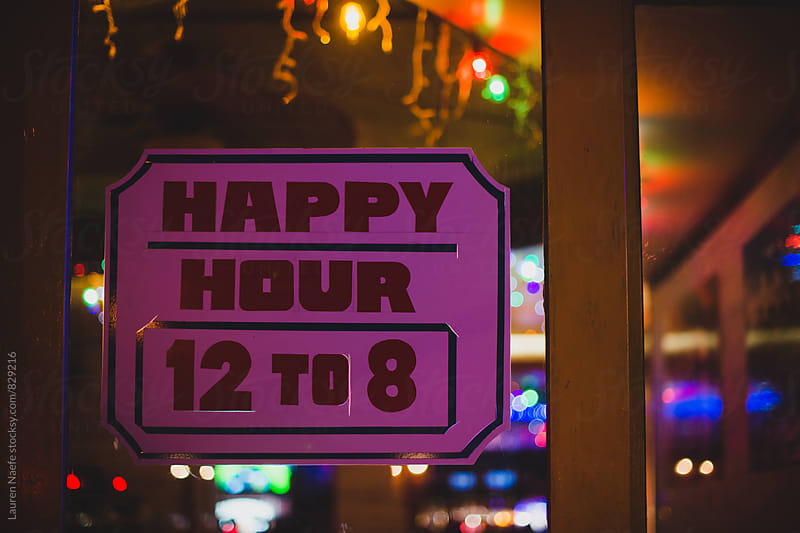 Happy hour sign at night by Lauren Naefe for Stocksy United