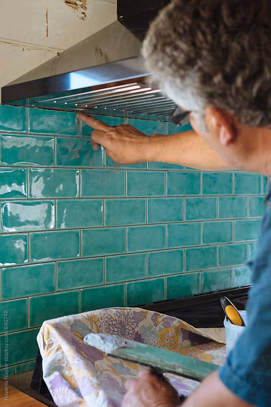 Tiler grouting kitchen tiles by Rowena Naylor for Stocksy United