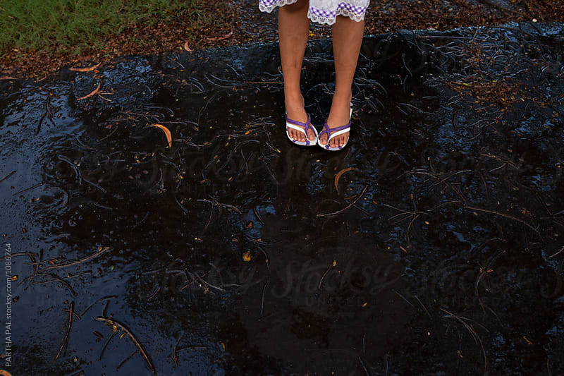 A teenage girl standing on a wet road caused by rain water by PARTHA PAL for Stocksy United
