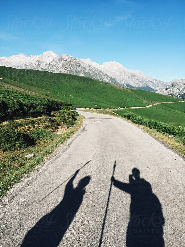 Shadows of two hiker walking on the road  by Luca Pierro for Stocksy United