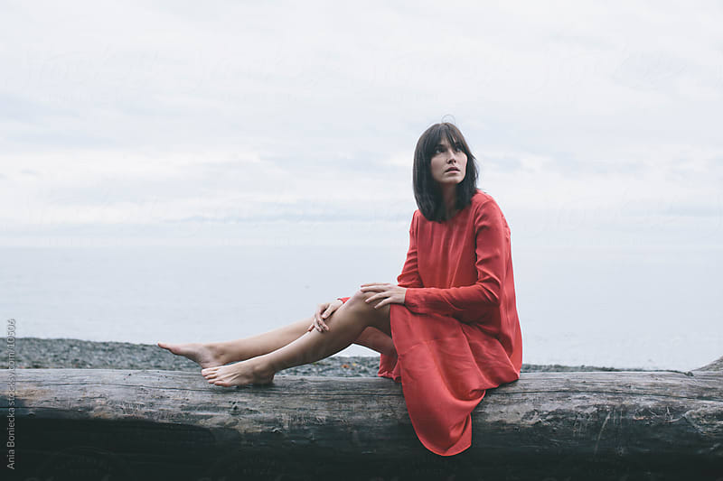 A woman in a red dress looking up by Ania Boniecka for Stocksy United