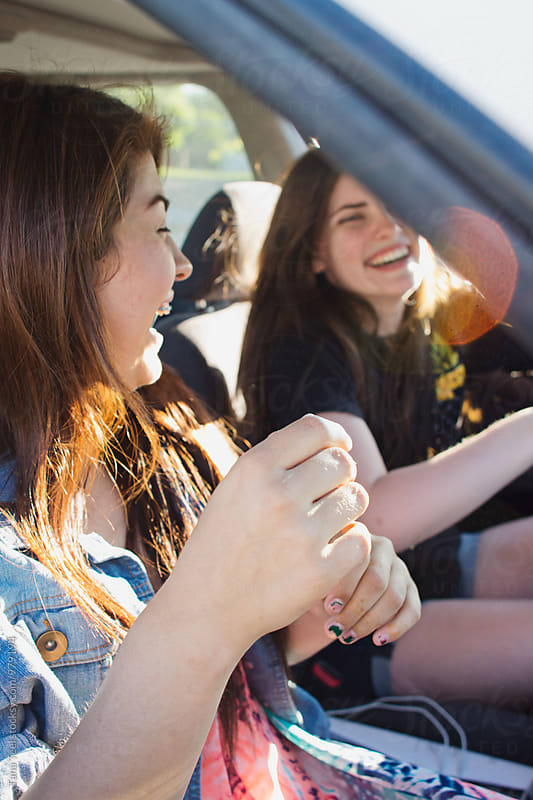Teenagers sitting in car laughing by Tana Teel for Stocksy United