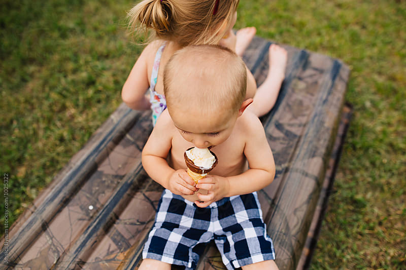 Toddler boy eating an ice cream cone by Jessica Byrum for Stocksy United