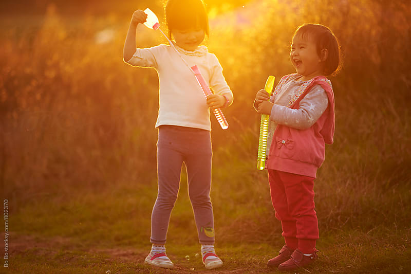 two happy asian kids blowing bubble outdoor by cuiyan Liu for Stocksy United