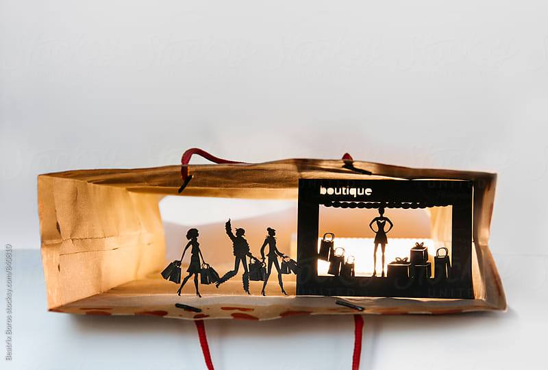 Concept: shopping women cut out of cardboard in a real shopping bag with big copyspace by Beatrix Boros for Stocksy United