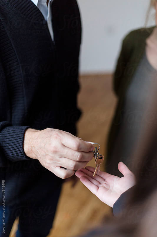 An agent handing new appartmant keys to the buyers by Jovana Milanko for Stocksy United