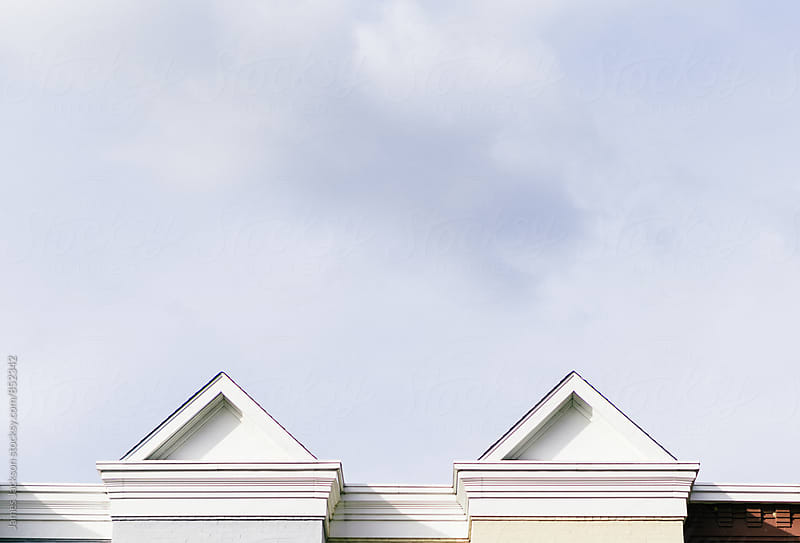 Two Federal style rowhouse rooftop peaks. by James Jackson for Stocksy United
