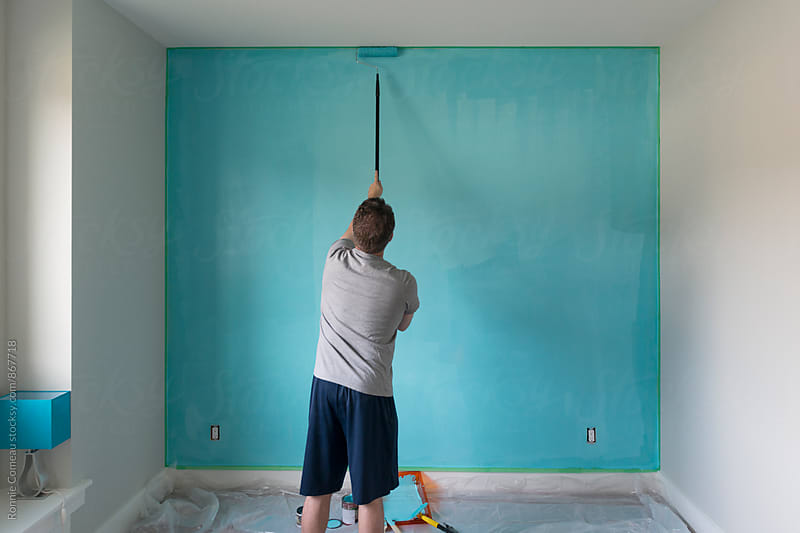 Man Painting A Wall Blue by Ronnie Comeau for Stocksy United