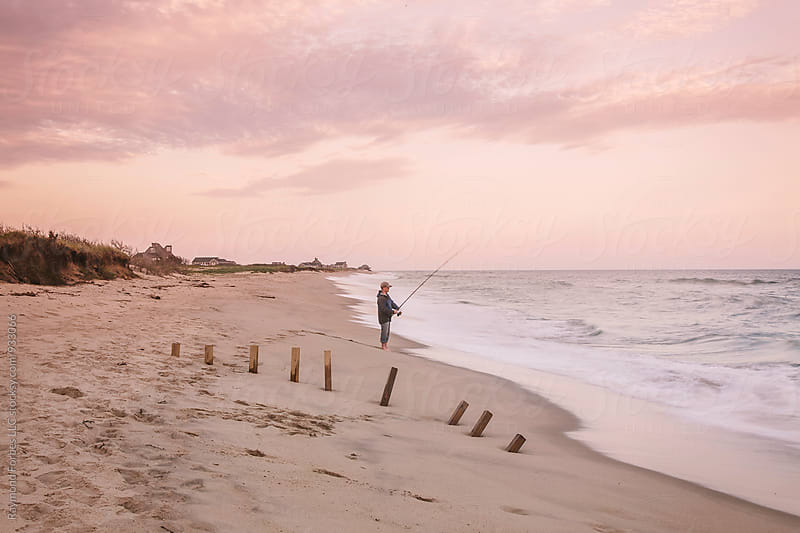 Man Surfcasting at Sunset on Nantucket Island by Raymond Forbes LLC for Stocksy United
