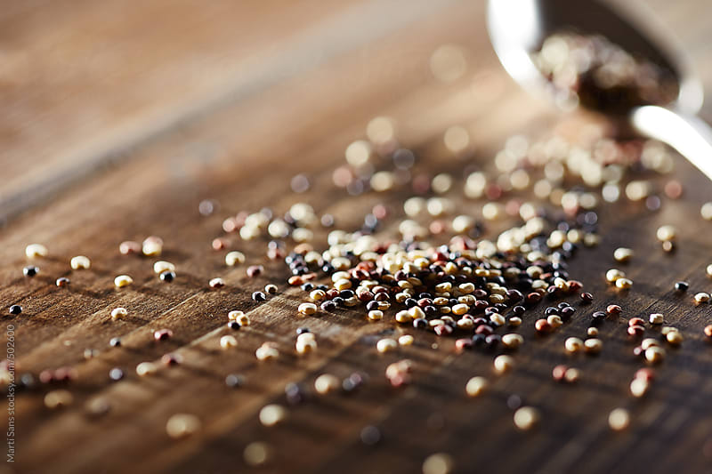 Raw quinoa on wooden table close-up by Martí Sans for Stocksy United