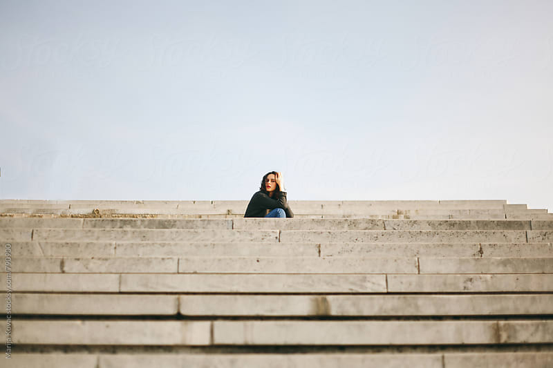 Woman sitting on the stairs - horizontal by Marija Kovac for Stocksy United