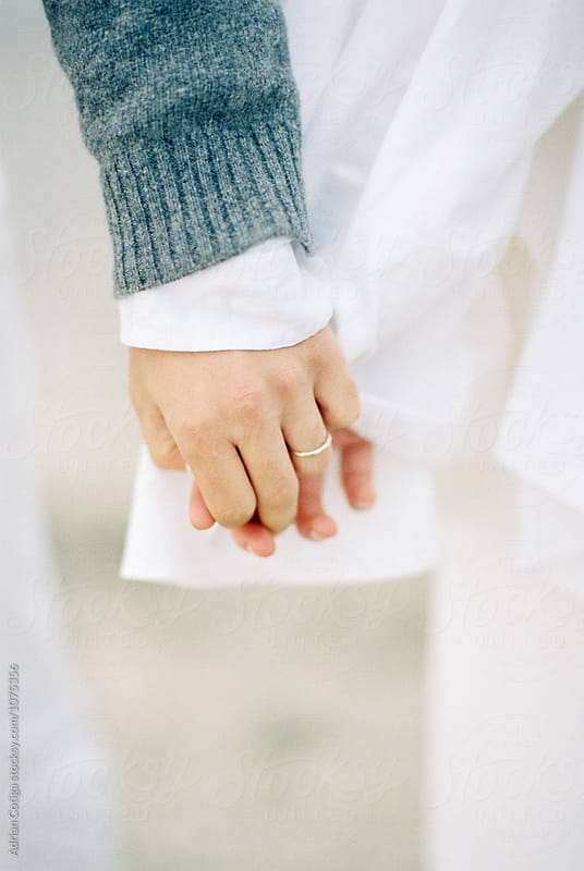 Married couple holding hands by Adrian Cotiga for Stocksy United