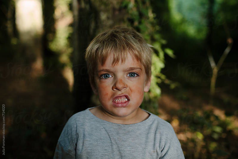 Boy covered in red clay dust bares his teeth while pretending to be a tiger in a forest. by Julia Forsman for Stocksy United